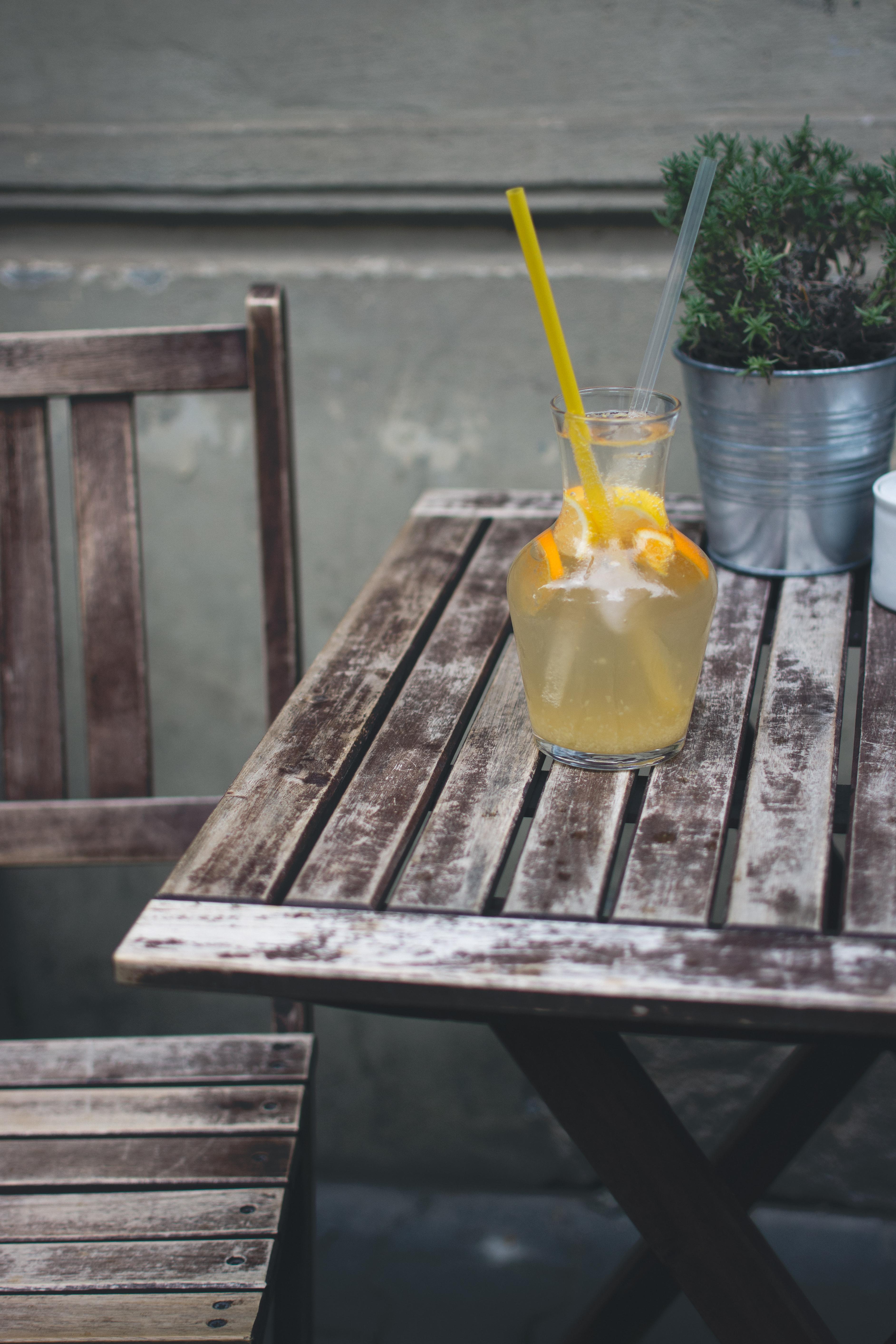 Orange lemonade at a wooden desk outside
